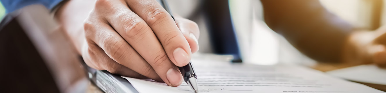 Close of of hand holding a pen to paper document.