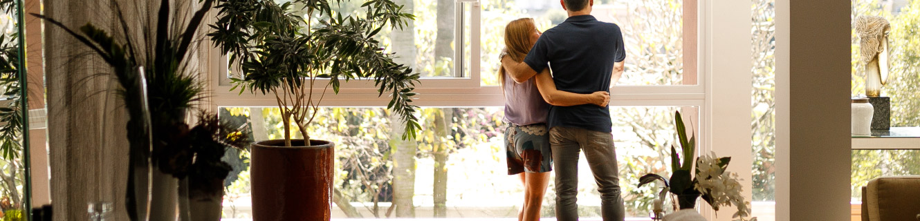 Mature couple looking out the living room window.
